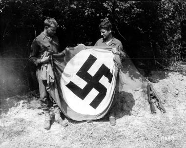 Deux GI's et leur trophée, un drapeau du parti nazi. Celui de droite appartient à la 2nd US Armored Division. Voir ici l'insigne d'épaule: http://www.flickr.com/photos/mlq/2385533436/